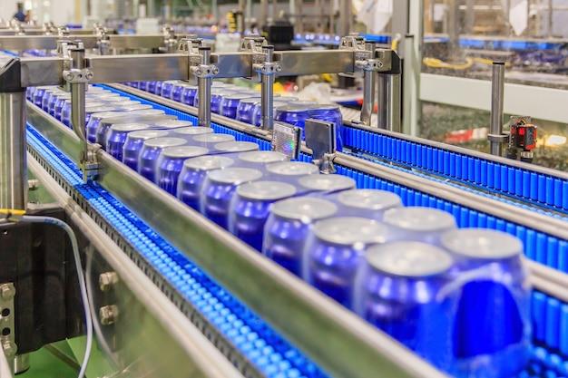 Verpackte dosen auf dem förderband in der getränkefabrik