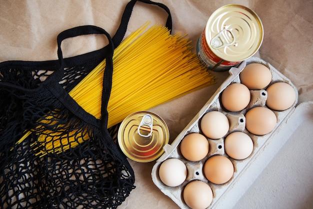 Verpackte eier, konserven, nudeln, produkte in einer umweltfreundlichen tasche auf einem hintergrund aus ökologischem papier. vegetarische gesunde bio-lebensmittel vom markt. spende für bedürftige.