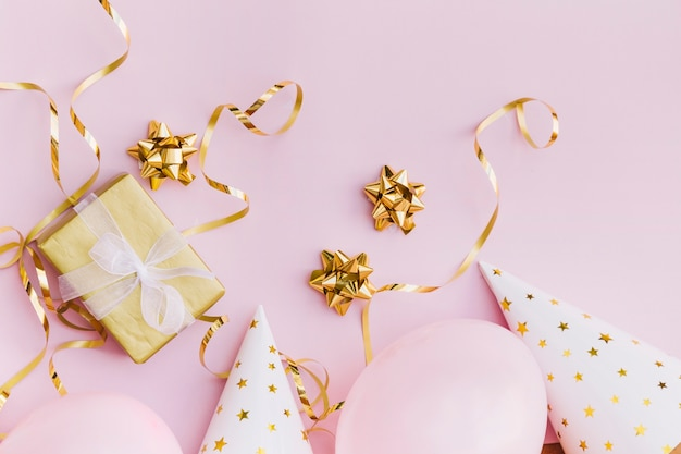 Verpackte geschenkbox; bogen; streamer; ballon und partyhut auf rosa hintergrund
