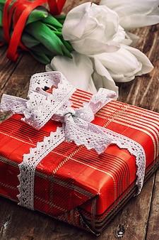 Verpackte geschenkbox inmitten eines straußes aus weißen tulpen
