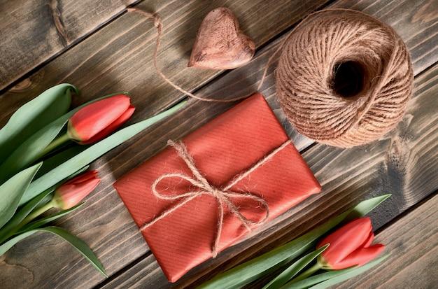 Verpackte geschenkbox, schnur und dekoratives herz auf holztisch