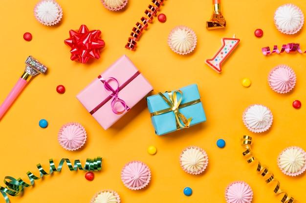 Verpackte geschenkboxen; aalaw; luftschlangen; edelsteine; und verpackte geschenkboxen vor gelbem hintergrund