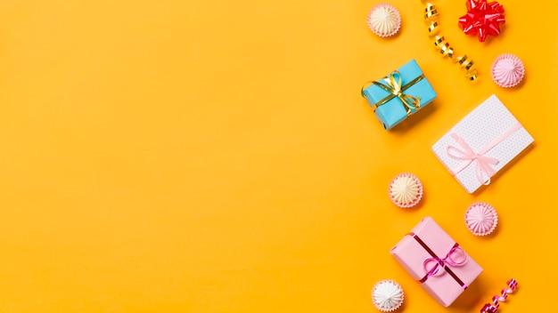 Verpackte geschenkboxen; aalaw; luftschlangen und eingewickelte geschenkkästen auf gelbem hintergrund