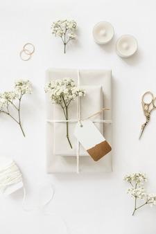 Verpackte geschenkboxen mit babyatmungsblumen und anhänger mit kerzen; schere und eheringe