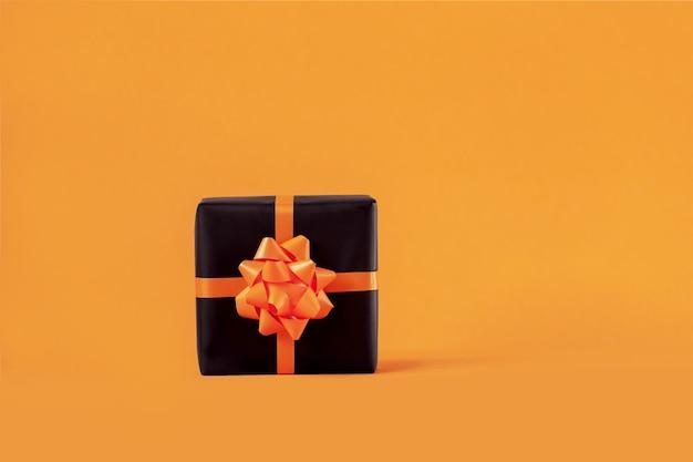 Verpackte handgemachte geschenkbox aus schwarzem papier mit schleife auf orangem hintergrund. halloween- und geburtstagskonzept.