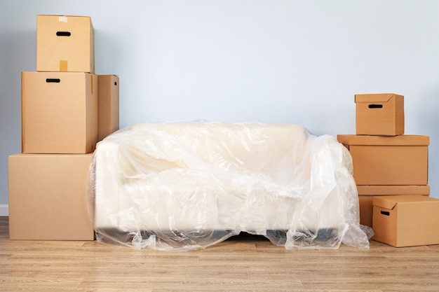 Verpackte haushaltsgegenstände in kisten und gepacktes sofa zum bewegen