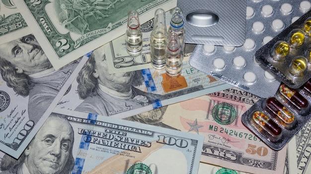Verpackte medizinische pillen und kapseln auf dollarnoten, ansicht von oben