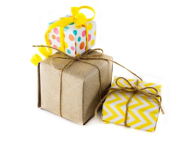 Verpacktes geschenk in farbigem, gelbem und kraftpapier auf einer weißen oberfläche