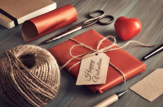 Verpacktes geschenk, verpackungsmaterialien, papptags und und steinherz auf holz, text