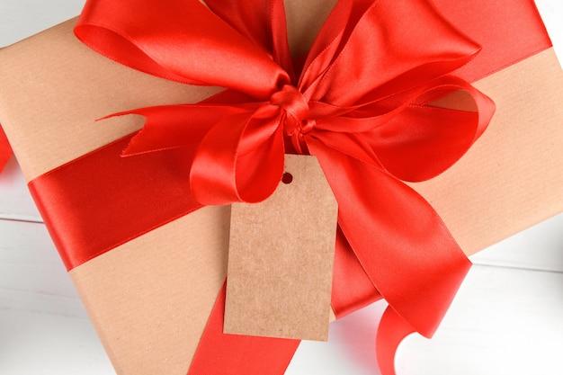 Verpacktes geschenkpaket aus bastelpapier mit tag-geschenk, nahaufnahme. mit einem paketanhänger und einem roten band gekrönt.