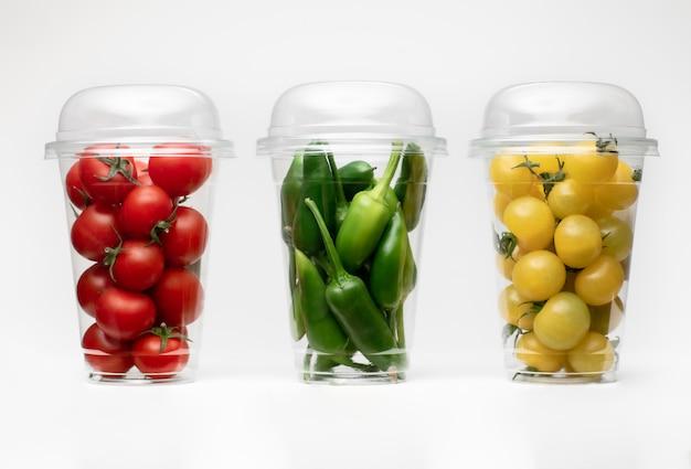 Verpackung mit grünem pfeffer und tomate auf weißem raum. isolierter weißer raum. tomaten isoliert.