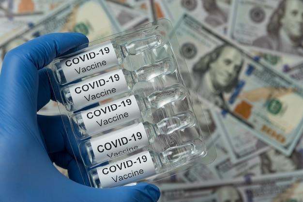 Verpackung von ampullen mit dem impfstoff covid-19 in der hand. nahansicht.