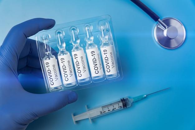 Verpackung von ampullen mit dem impfstoff covid-19 in der hand.