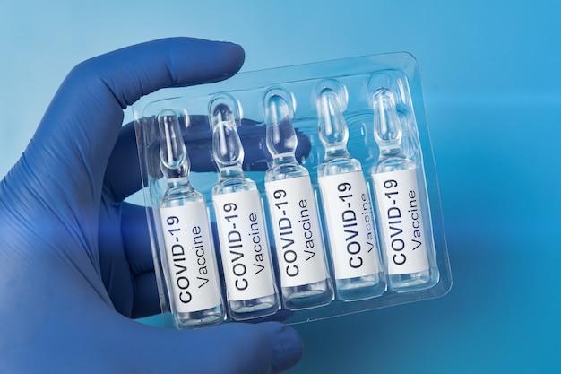 Verpackung von ampullen mit dem impfstoff kovid-19 in einer behandschuhten hand. nahansicht. pandemie-kontrollkonzept