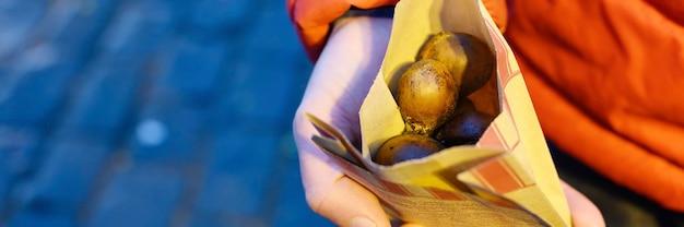 Verpackung von essbar gerösteten roten kastanien in den händen eines mannes auf der straße. winter gourmet essen.