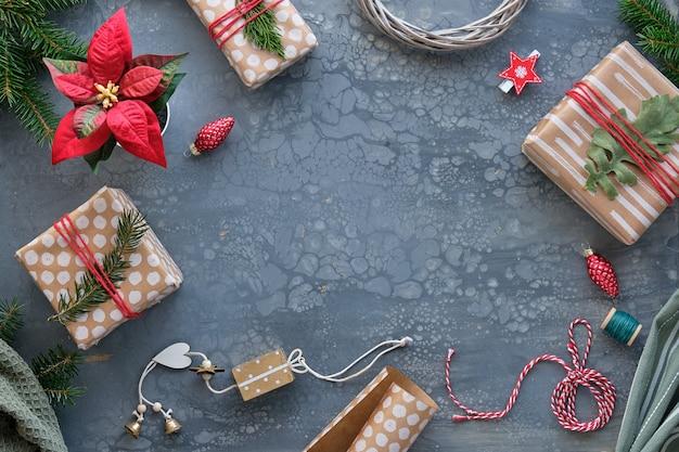 Verpackung von weihnachtsgeschenken, geschenken, in bastelpapier, braunes papier mit abstrakten punkten und streifen. weihnachtshintergrund mit geschenkboxen, tannenzweigen, textil auf dunkelgrauem tisch mit kopierraum.