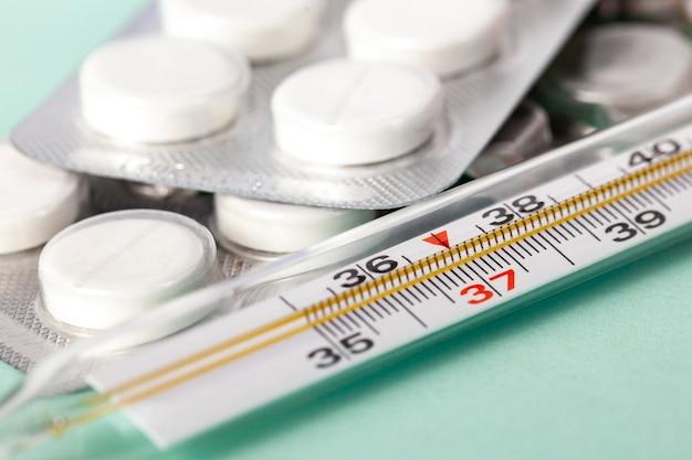 Verpackung von weißen tabletten, packungen von weißen pillen in blasen verpackt, thermometer