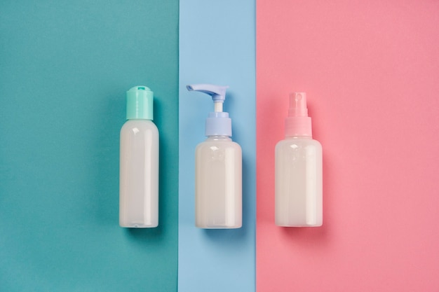 Verpackungen von creme, lotion, gel oder seife auf blauem und rosa hintergrund