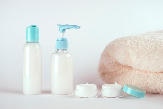 Verpackungen von creme, lotion, gel oder seife und einem handtuch auf weißem hintergrund