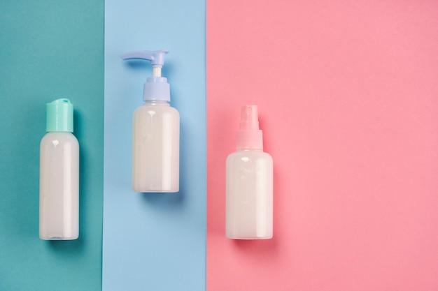 Verpackungen von seife, creme, lotion oder gel auf blauem und rosa hintergrund