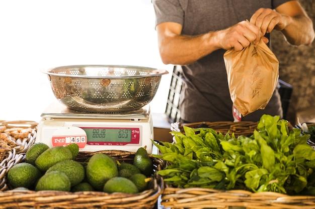 Verpackungsgemüse des männlichen gemüseverkäufers für kunden am markt