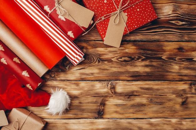 Verpackungspapierrollen für weihnachtsgeschenke auf der draufsicht des braunen holzbretts