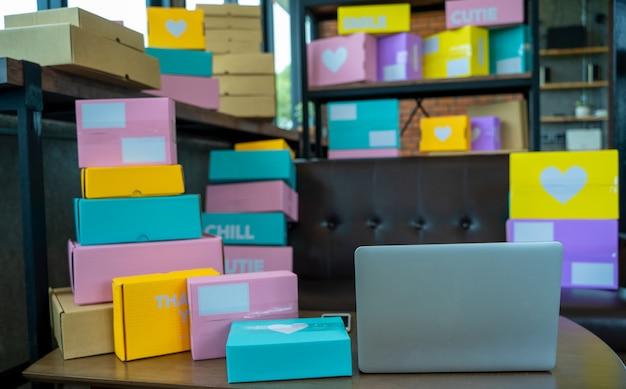 Verpackungszubehör am arbeitsplatz des start-up-kleinunternehmers, notebook, tablet, verpackungszubehör am arbeitsplatz des startup-kleinunternehmers, karton aus pappe für den online-verkauf, verkaufskonzept.