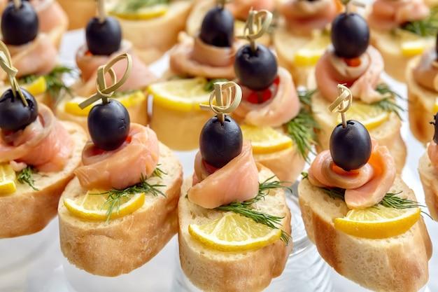 Verpflegung von canape mit oliven, zitrone und lachs