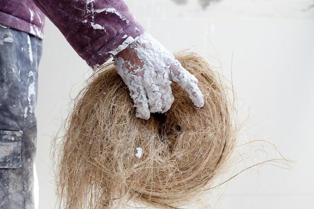 Verputzte schmutzige hand mit hanf für gipskartonplatten