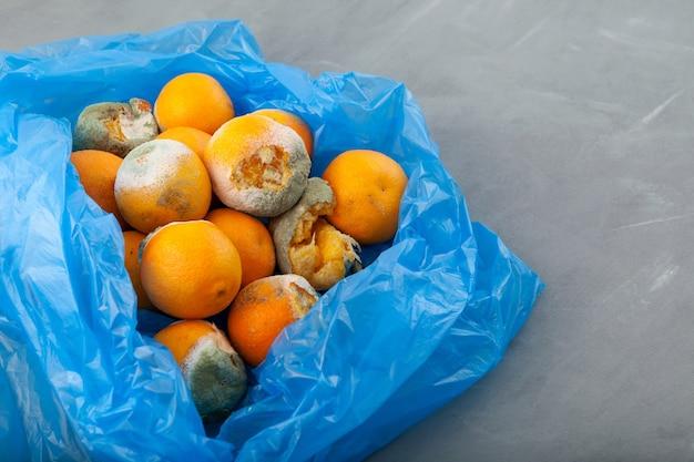 Verrottende mandarinen in blauer plastiktüte auf grau