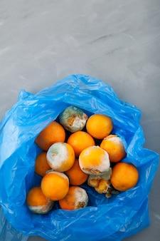 Verrottende mandarinen mit schimmel in blauer plastiktüte