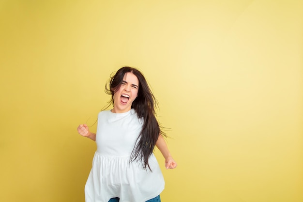 Verrückt glücklich, tanzend. kaukasische frau als osterhase auf gelbem studiohintergrund.