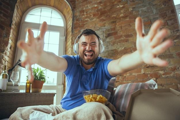 Verrückt glücklich über das lieblingsteam. videoanruf, soziale medien. fauler mann, der in seinem bett lebt, umgeben von unordnung. sie müssen nicht ausgehen, um glücklich zu sein. mit gadgets, filme und serien schauen, emotional. fast food.