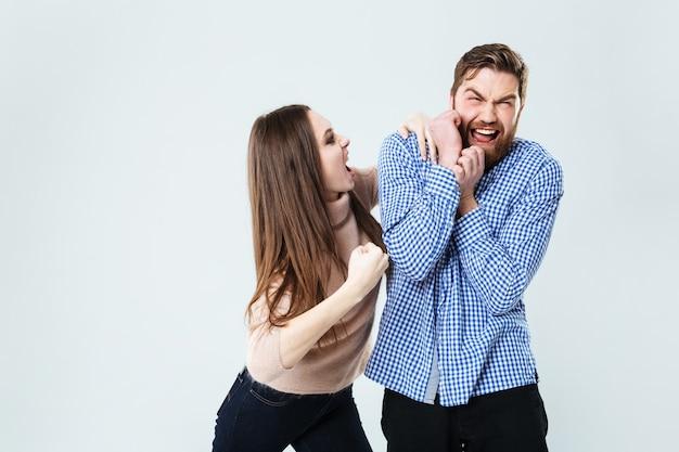 Verrückte aggressive junge frau, die mit ihrem mann über weiße wand schreit und kämpft