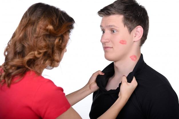 Verrückte betrogene frau und ihr ehemann mit lippenstift auf gesichtern.