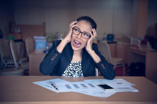Verrückte büroangestelltfrau, die am schreibtisch sitzt.