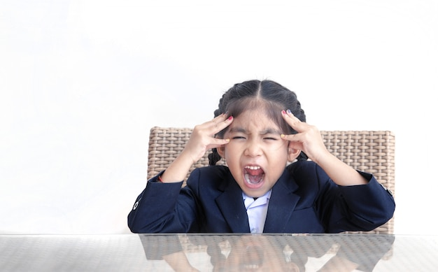 Verrückte emotion der asiatischen kinderaktion auf tisch mit weiß lokalisiert