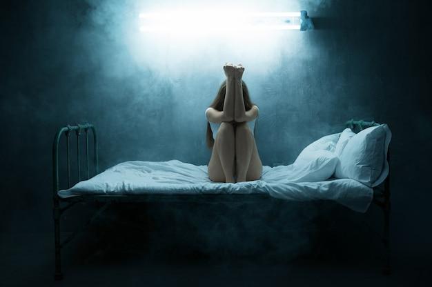 Verrückte frau, die im bett sitzt, schlaflosigkeit, dunkles zimmer. psychedelische weibliche person, die jede nacht probleme hat, depression und stress, traurigkeit, psychiatrisches krankenhaus