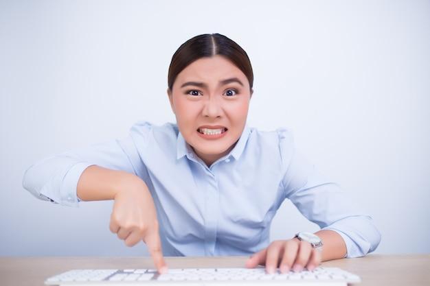 Verrückte frau mit den händen auf tastatur