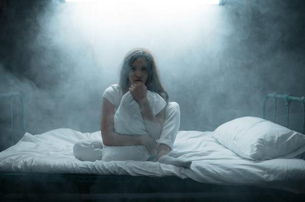 Verrückte frau mit kissen im bett sitzend, dunkles zimmer. psychedelische person, die jede nacht probleme hat, depression und stress, traurigkeit, psychiatrisches krankenhaus