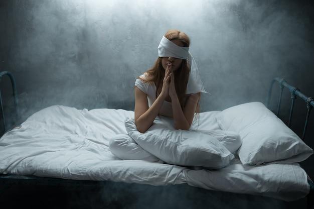 Verrückte frau mit verbundenen augen, die im bett sitzt, dunkles zimmer. psychedelische weibliche person, die jede nacht probleme hat, depression und stress, traurigkeit, psychiatrisches krankenhaus
