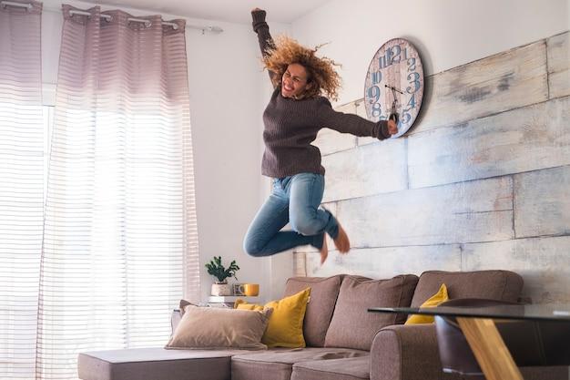Verrückte frau mittleren alters springt zu hause über das sofa, um den erfolg zu feiern