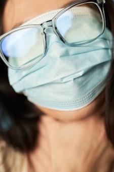 Verrückte frau posiert im studio mit antivirus-maske und brille, während sie ihren kopf hält