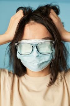 Verrückte frau posiert im studio mit antivirus-maske und brille