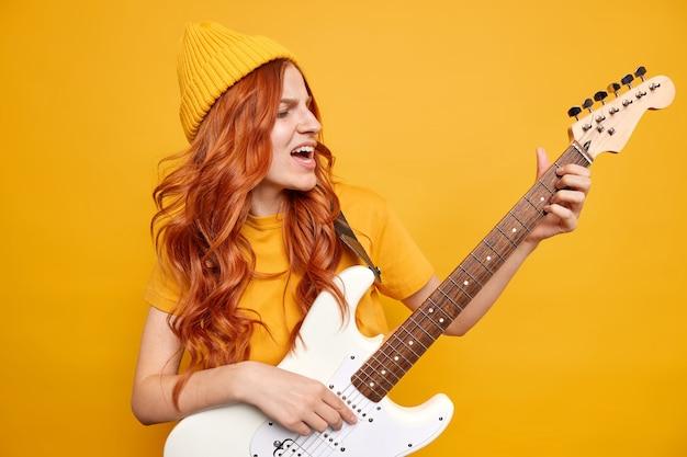 Verrückte fröhliche künstlerin führt rockmusik auf elektrischer akustikgitarre auf, trägt hut und t-shirt hat natürliches rotes haar, singt berühmte legendenliedposen gegen leuchtend gelbe wand. unterhaltung