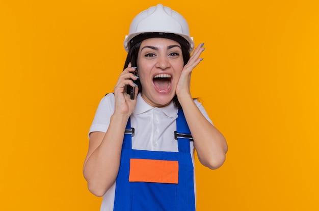 Verrückte glückliche und aufgeregte junge baumeisterfrau in der bauuniform und im sicherheitshelm, die auf handy sprechen, das über orange wand steht