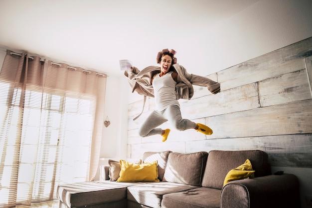 Verrückte hausfrau allein springt auf das sofa für glücks- und erfolgsnachrichten
