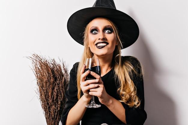 Verrückte hexe, die blut auf weißer wand trinkt. spektakulärer weiblicher zauberer, der weinglas mit trank hält.