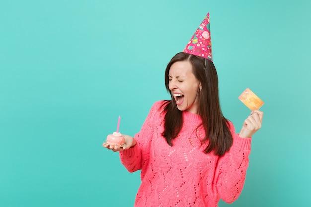 Verrückte junge frau in gestricktem rosa pullover, geburtstagshut schreiend, kuchen in der hand haltend mit kerzenkreditkarte einzeln auf blautürkisem wandhintergrund. menschen lifestyle-konzept. kopieren sie platz.