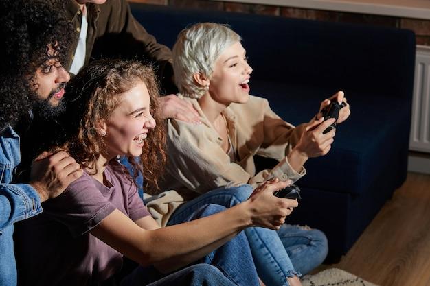 Verrückte junge leute freunde, die das spielen von videospiel-spielkonsolen genießen, zu hause ausruhen, zu hause ausruhen, in freizeitkleidung, spielekonsole